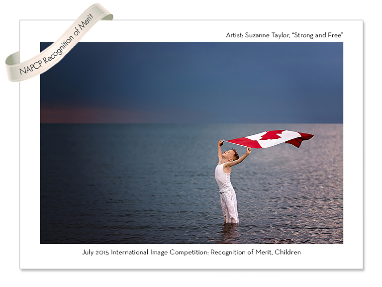Young boy dressed in white holding the Canada Day Flag above his head with the wind blowing it