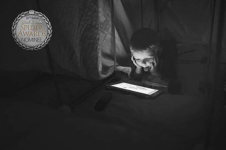 Young boy under a fort watches a show on the iPad with his tongue sticking out.