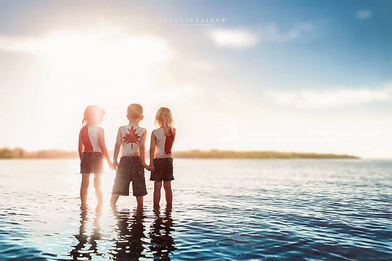 Triplets stand in Gull Lake, Alberta with the Canada Day Flag painted on their backs at sunset