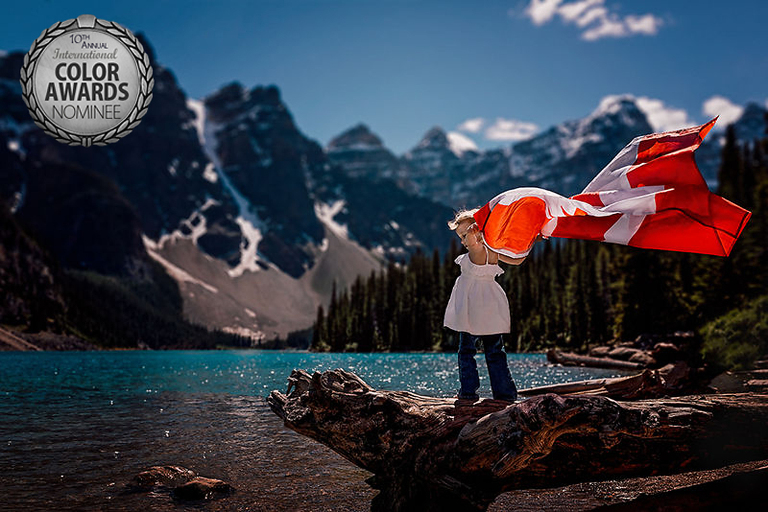 Young girl holds Canada Day flag above her head at Moraine Lake, Alberta in Lake Louise.